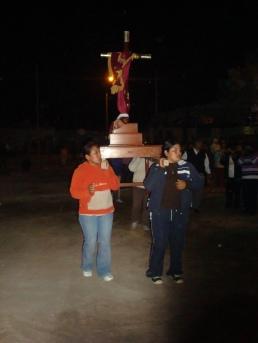 Mujeres del pueblo portando la cruz
